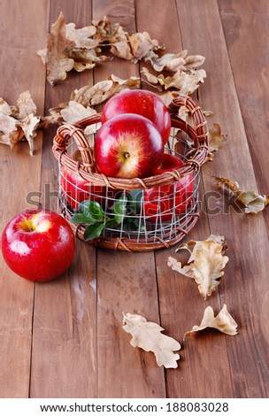 Red organic apples in a metal basket on wooden background  - stock photo