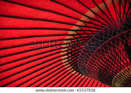 Red oriental paper umbrella open in bright sunlight - stock photo