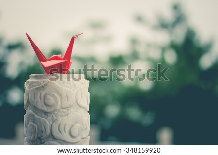 Red origami crane on the marble asian slab (soft focused) - stock photo