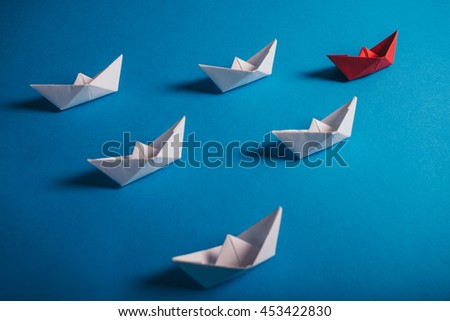 Red origami paper ship with its fleet. Concept for leadership, management, motivation, difference and uniqueness. - stock photo