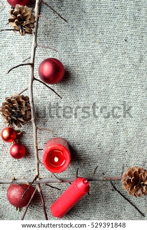 Red ornament balls with red candles.frame.knit fabric background