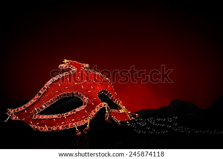 Red ornate Venice mask with black pearls near. Red and black background - stock photo