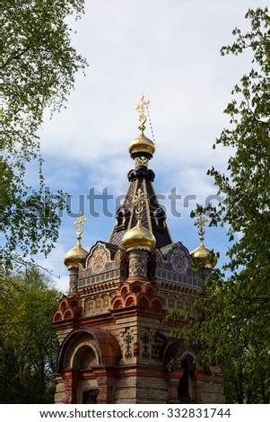 Red orthodox church with traditional decoration in a park