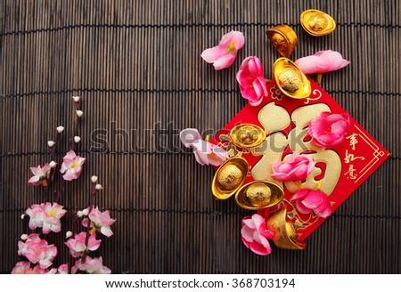 "Red packet , Shoe-shaped gold ingot (Yuan Bao) and both with Chinese character ""Fu"" means fortune on top) and Plum Flowers over bamboo mat with copy space - best for Chinese New Year use - stock photo"