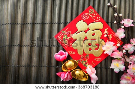 "Red packet , Shoe-shaped gold ingot (Yuan Bao) both with Chinese character ""Fu"" means fortune on top and Plum Flowers over bamboo mat with copy space - best for Chinese New Year use - stock photo"
