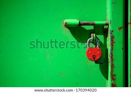 Red padlock and very green door - stock photo