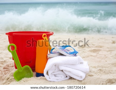 Red pail, sun cream, shovel and towel with flippers on it on ocean beach - stock photo