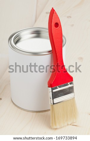 Red paint brush with paint bucket on wooden planks - home renovation or diy concept - stock photo