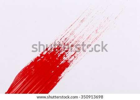 Red paint splash on a white paper - stock photo