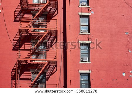 Red painted and weathered facade with outside fire escape and windows with room air conditioner