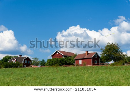 Red painted farm houses in luscious greenery under a bright blue sky in summerly Sweden