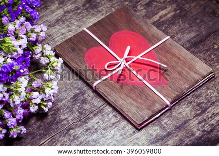 Red painted  heart on wooden with flower on wooden background - stock photo
