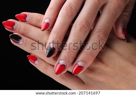 Red painted nails and hands isolated on black background
