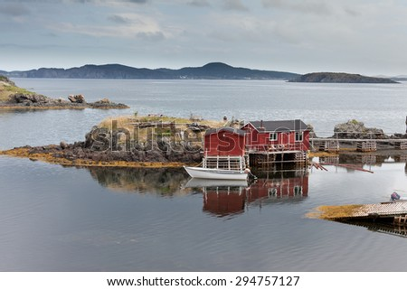 Red painted wooden fishing shacks at New Foundland, NL, Canada, Atlantic Ocean coast calm cove