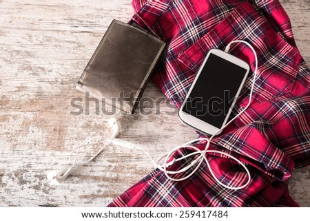 Red pants, a wallet and a smartphone with plugged in earphones on the table.	  - stock photo