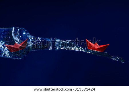 Red paper boat rides on a water splash out of the bottle, another waits for freedom inside at the bottleneck, dark blue background, concept for get away, escape or liberation - stock photo