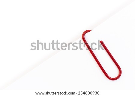 Red paper clip on white paper - stock photo