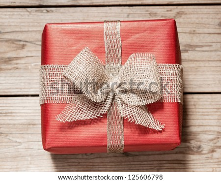 red paper gift box with bow on wooden background