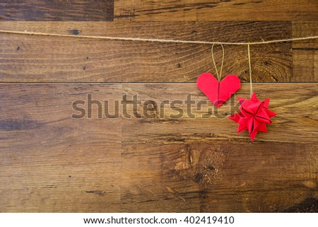 Red paper heart and origami star hanging on the clothesline on wooden background. Vintage style. Concept image for Christmas holidays. Postcard on wood texture with copy space for text.  - stock photo
