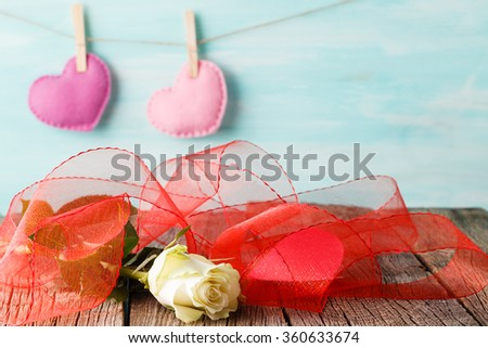 Red paper heart hanging on the clothesline. On aquamarine wood background