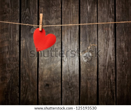 Red paper heart hanging on the clothesline. On old wood background. - stock photo