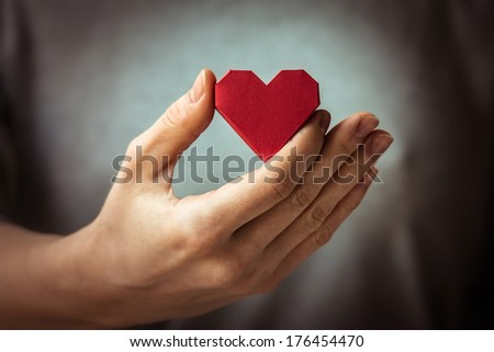 Red paper heart in woman hands - stock photo