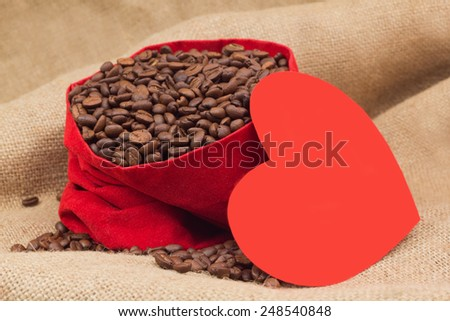 Red paper heart next to velvet red sac with coffee beans - stock photo