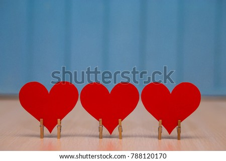 Red paper Heart of love with wooden clips on table with blue wooden background. Romantic symbol. Love concept
