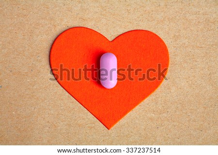 Red paper heart shape over craft paper with one small pink pill on. Heart health concept.  - stock photo
