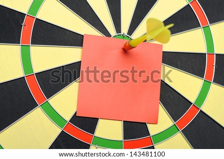 Red paper note with dart arrow on dartboard. You can put your message on the paper - stock photo