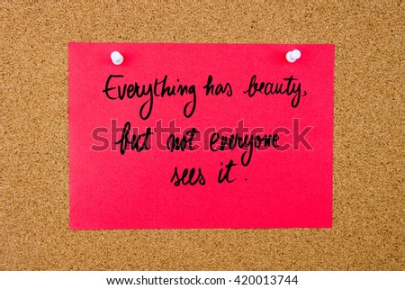 Red paper note with handwritten text Everything Has Beauty, But Not Everyone Sees It pinned on cork board with white thumbtacks - stock photo