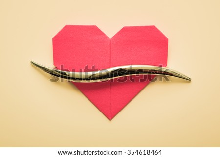 Red paper Valentine's Day heart against the door handle. - stock photo