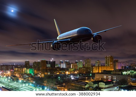 Red passenger plane in moonlight. Aircraft is flying over the night city. - stock photo