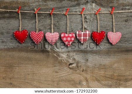 Red patterned  Valentine's hearts hanging on rustic Elm wooden texture background, copy space - stock photo