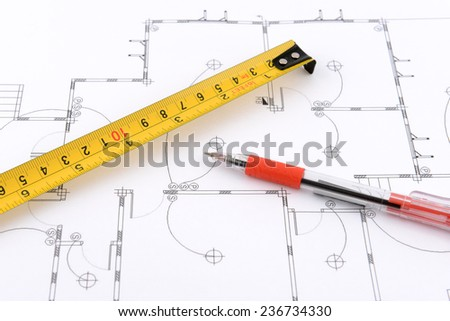 red pen and measuring tape on plans - stock photo