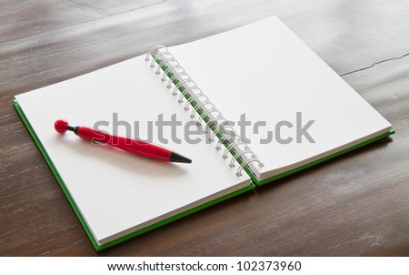 Red pen and notepad on wooden table - stock photo