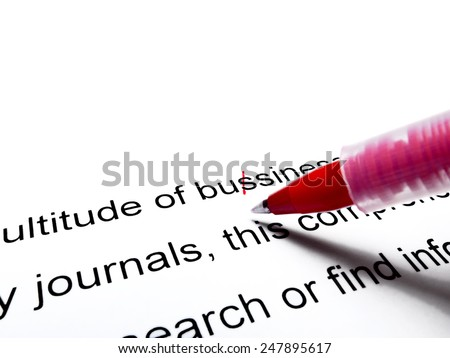 Red pen correcting proofread english text close up