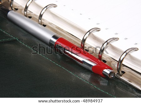 Red pen lying on an open green organizer