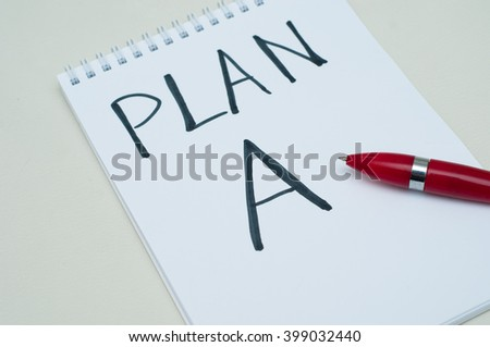 Red pen on the notebook. On white. - stock photo