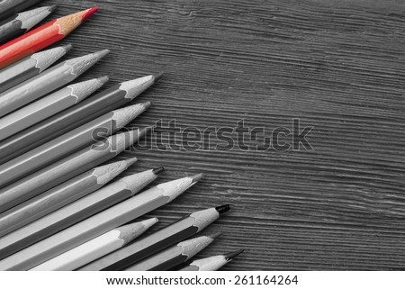 Red pencil among black and white - stock photo