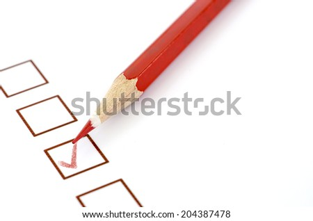 Red pencil and questionnaire on white paper