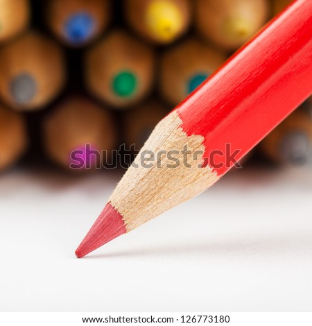 red pencil draws or writing on white paper sheet, colored pencils as background - stock photo