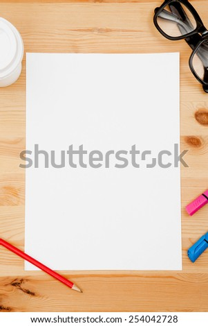 Red pencil, eye glasses, disposable coffee cup and sheet of paper on wooden table. Background for text. - stock photo