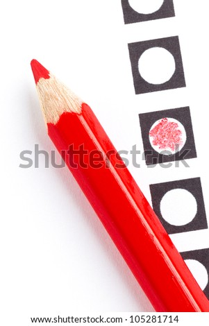 Red pencil on a voting form, isolated on white - stock photo