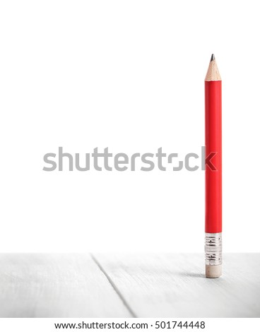 red pencil on wooden plank and white background
