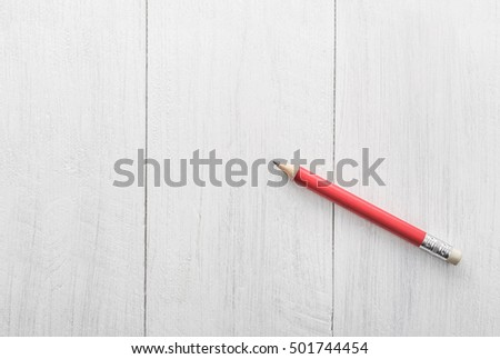 red pencil on wooden white background
