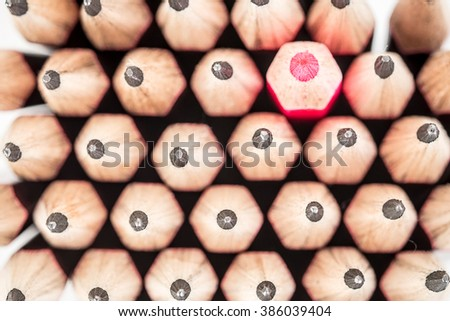 Red pencil standing out from crowd of black fellows on white background. Leadership, uniqueness, think different, business success concept - stock photo