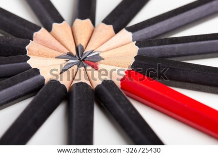 Red pencil standing out from crowd of plenty identical black fellows on white table. Leadership, uniqueness, independence, initiative, strategy, dissent, think different, business success concept - stock photo