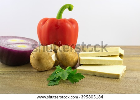 Red pepper, bit of parsley, mushrooms, red onion and sliced tofu on wooden plate against white background, selective focus on parsley  - stock photo