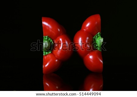 Red pepper cutting on half isolated on black background